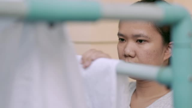 ハンガーに濡れ床を掛ける女性 - 楽しい 洗濯点の映像素材/bロール