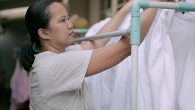ハンガーに濡れたベッドシーツをぶら下げる女性 - 楽しい 洗濯点の映像素材/bロール