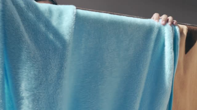 Woman hanging wet blanket on hanger
