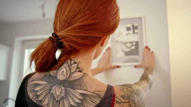 kvinna hänger en bild i ett nytt hem. - hänga bildbanksvideor och videomaterial från bakom kulisserna