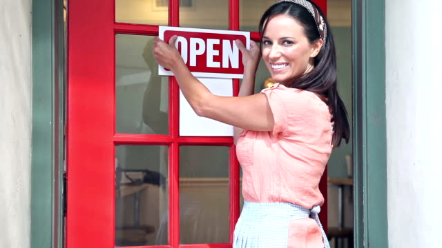 Woman hangs OPEN sign on outside of door Small business owner - a mid adult woman in her 30s exits the front door of the shop and hangs an OPEN sign on the door. opening event stock videos & royalty-free footage