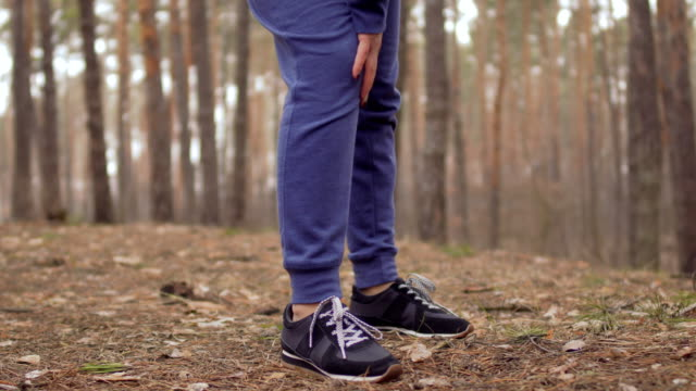 Woman has a pain in her knee during morning exercises in the forest Woman stands in front of camera and holding by his knee. The sportswoman suffers from pain in her leg, but continue her train in the forest. knee stock videos & royalty-free footage