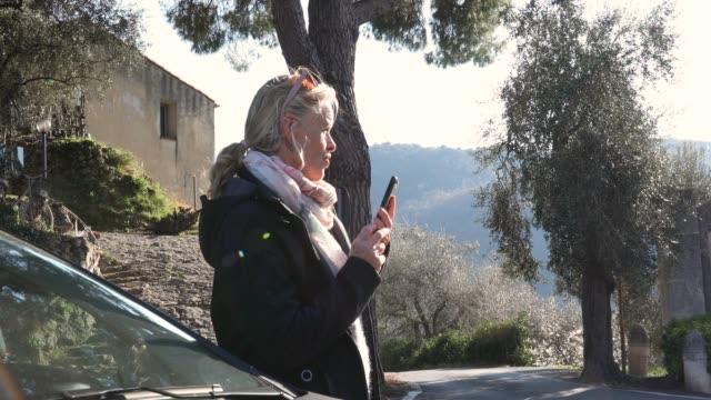 vídeos de stock e filmes b-roll de woman has smart phone conversation beside car - 55 59 anos