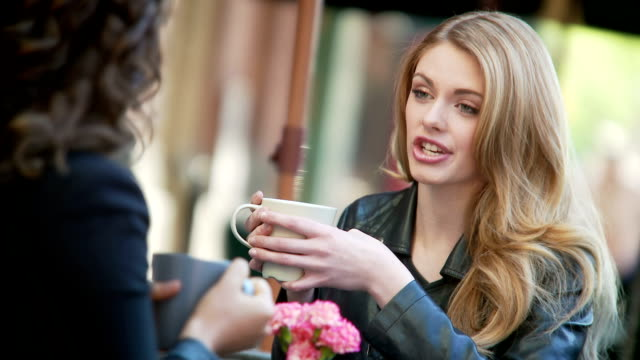 Woman have a chat while enjoying latte. video
