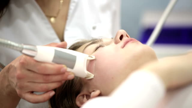 Woman have a massage for reducing face. Electronic massage system video