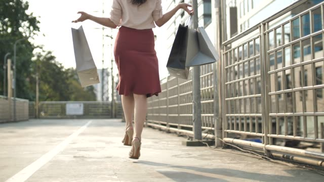 Woman have fun walking and jumping on the street with Shopping bag their purchases after shopping, Happy time