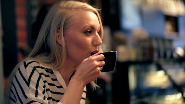 woman having a conversation in coffeeshop Video clip of a woman sitting smiling in a coffeeshop drinking coffe and talking to friends and people pass by in background sideways glance stock videos & royalty-free footage