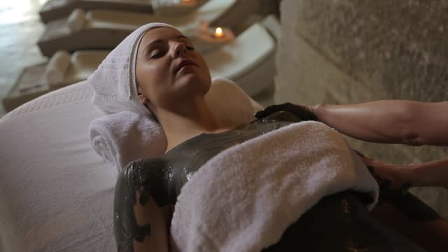 woman having a mud massage in a spa - video