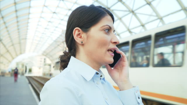 Woman having a phone call. Woman having a phone call while waiting the tram. She is going to her job or to a meeting. Public transportation saves time and energy. railroad station platform stock videos & royalty-free footage
