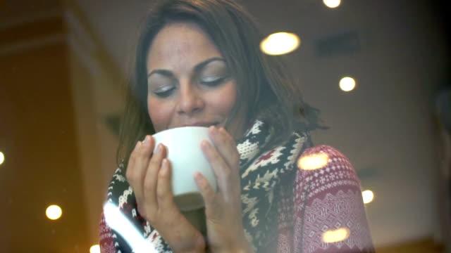 donna avendo una tazza di tè o caffè sulla neve giorno. - abiti pesanti video stock e b–roll