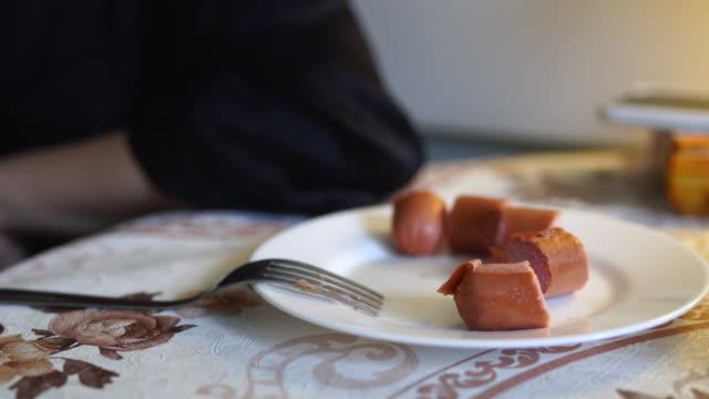 frau beim frühstück zu hause, teller mit würstchen und tasse kaffee - koffeinmolekül stock-videos und b-roll-filmmaterial