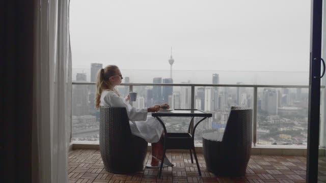 Woman Having Breakfast Young woman enjoying the fresh aroma of her first cup of coffee for the morning on a terrace with view over city in slow motion. hotel stock videos & royalty-free footage