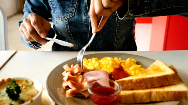 Woman having breakfast  with eggs bread hotdog video