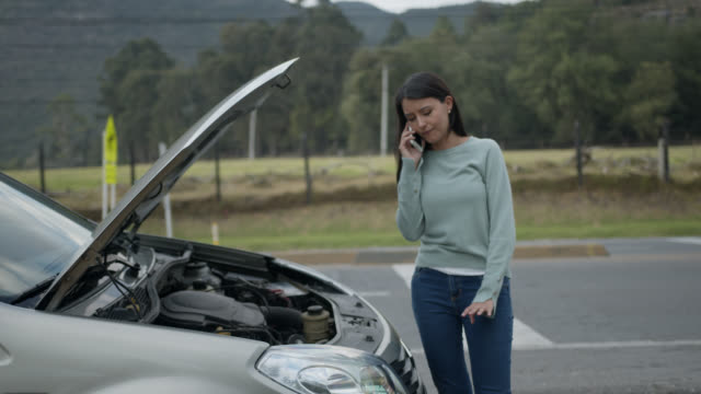 Woman having car trouble with the vehicle hood open while on a phone call with the insurance