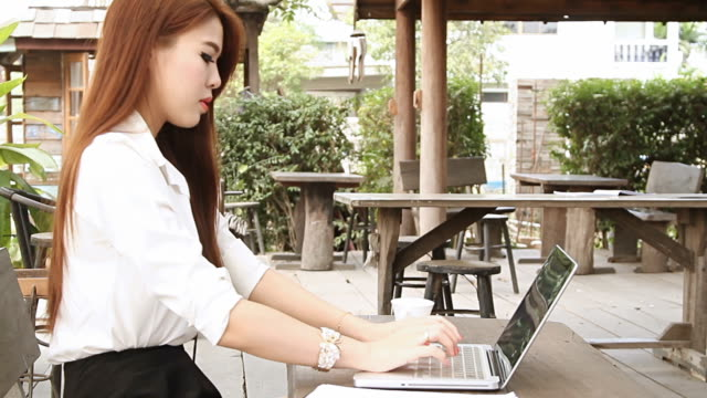 Woman having coffee and using laptop computer video