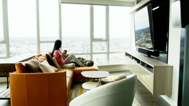 4 k のリビング ルームでコーヒーを飲んでいる女性 - 居間点の映像素材/bロール