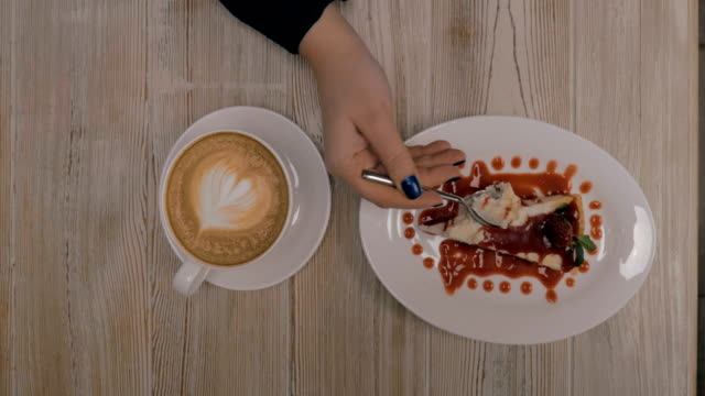 Woman having dessert with coffee in restaurant video