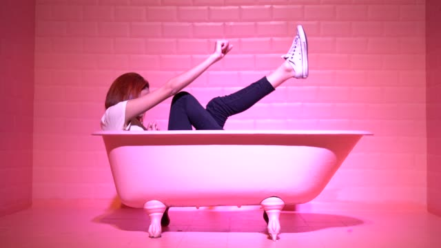 Woman Having Fun and Dancing in the pink bathtube video