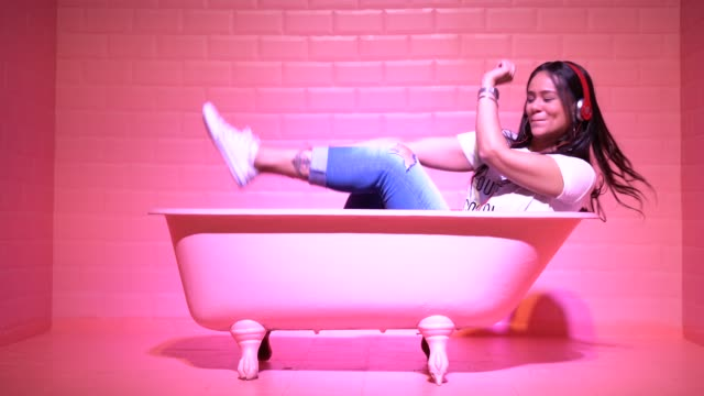Woman Having Fun and Dancing in the pink bathtube