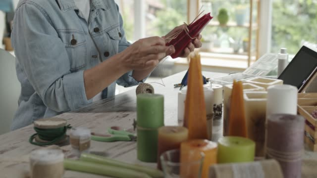 Woman having fun and enjoying decorating candles as a hobby Video of a happy mature woman enjoying and having fun while wrapping a piece of string around a candle and tying it into a bow while making decorations and doing arts and crafts during quarantine. craftsperson stock videos & royalty-free footage