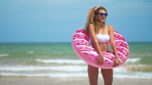 Woman having fun and smile dancing with pink donut. girl in bicini wearing sunglasses on the beach. Beautiful sexy woman on summer travel vacation