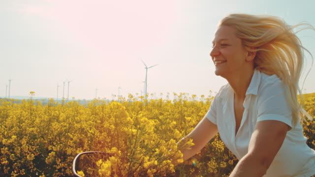 stockvideo's en b-roll-footage met super slo mo-time warp effect vrouw met plezier fietsen langs koolzaadvelden met windturbines in de verte - mid volwassen vrouw