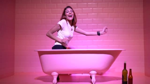 분홍색 bathtube에서 여자 재미 - 와인병 스톡 비디오 및 b-롤 화면
