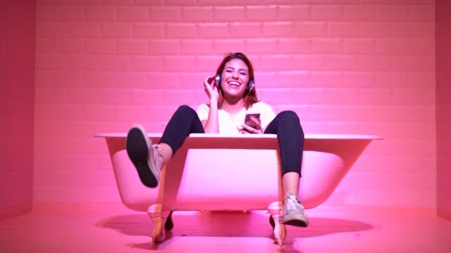 Woman Having Fun in the pink bathtube