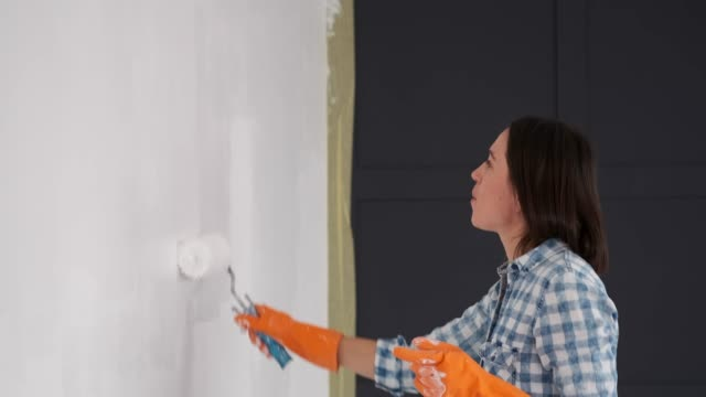 Woman having fun while painting wall with a roller video