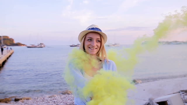 Woman having fun with smoke bomb on the beach