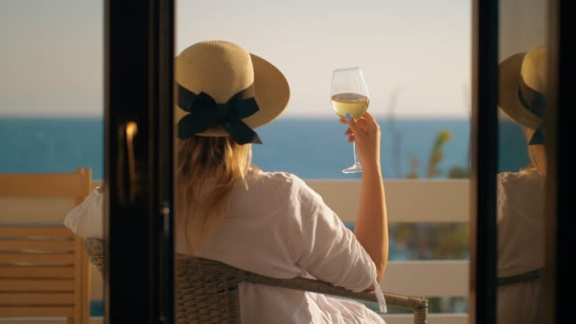 kvinna med bra tid dricka vin på balkongen med utsikt över havet - strandnära bildbanksvideor och videomaterial från bakom kulisserna