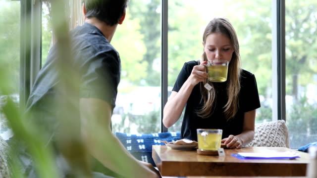 frau mit grünem tee im gespräch mit freund im café - grüner tee stock-videos und b-roll-filmmaterial