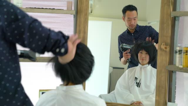 サロンで美容師で乾燥した彼女の髪のブローを持つ女性 - 美容院点の映像素材/bロール