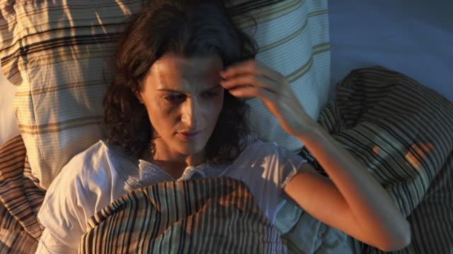 HD CRANE: Woman Having Insomnia HD1080p: CRANE shot of a worried mid-adult woman lying in bed sleepless at night. insomnia stock videos & royalty-free footage