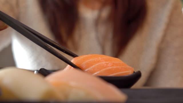 Woman having Japanese sushi in restauran Woman having Japanese sushi in restauran tuna seafood stock videos & royalty-free footage