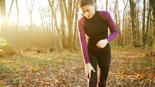 woman having pain on her knee while jogging. - fare fatica video stock e b–roll