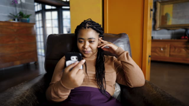 Woman having video call from her friend Afro woman sitting in armchair and using smart phone plus size model stock videos & royalty-free footage