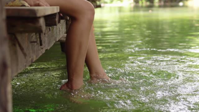 kvinna han lycklig och sitter på en träpir och dinglar fötterna i vattnet - flod vatten brygga bildbanksvideor och videomaterial från bakom kulisserna