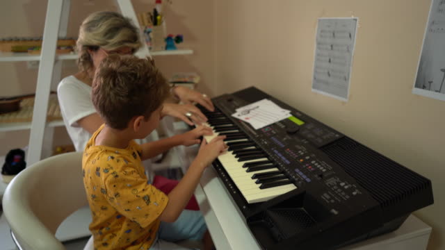 Woman helping little boy with playing synthesizer during music therapy at rehabilitation center