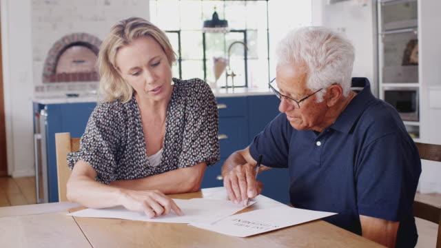 vídeos de stock, filmes e b-roll de homem sênior de ajuda da mulher para terminar a última vontade e o testamento em casa - assistente jurídico