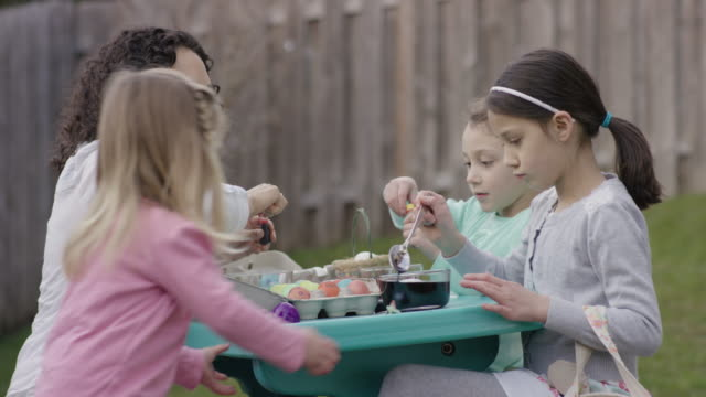 Woman helping young girls decorate Easter eggs video