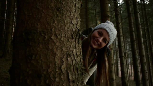 Woman hiding behind the tree video