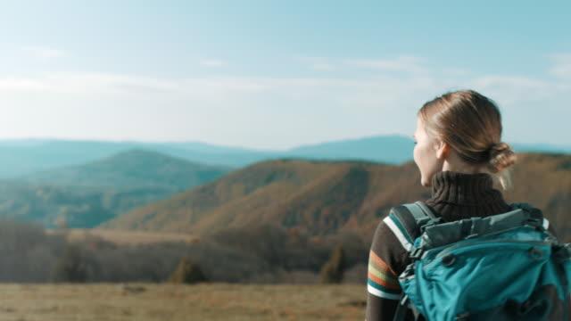 vídeos de stock, filmes e b-roll de alpinista de mulher no topo da montanha olhando na distância - distante