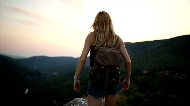 女性ハイカーが山の頂上で腕を開く ビデオ