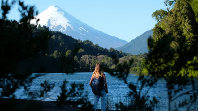 Woman hiker stands on the lake's coast with volcano of Osorno on the background, Chile