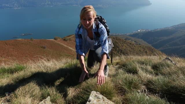vídeos de stock e filmes b-roll de mulher caminhada tem último passo para alcançar o topo da montanha - lago maggiore