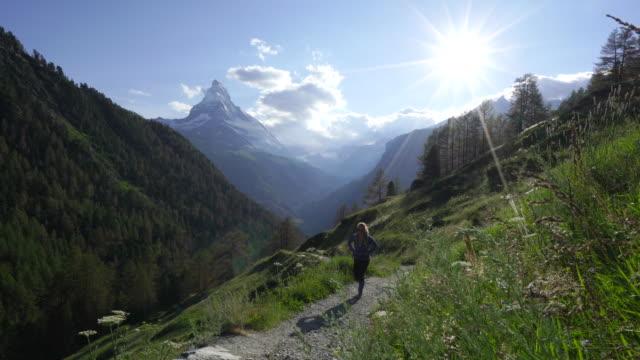 stockvideo's en b-roll-footage met vrouw wandelingen alpine trail met zonsondergang van zwitserse matterhorn - matterhorn