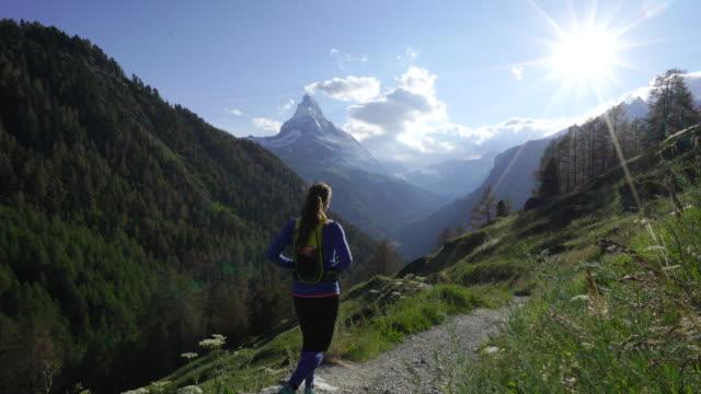 Woman hikes alpine trail with sunset view of Swiss Matterhorn