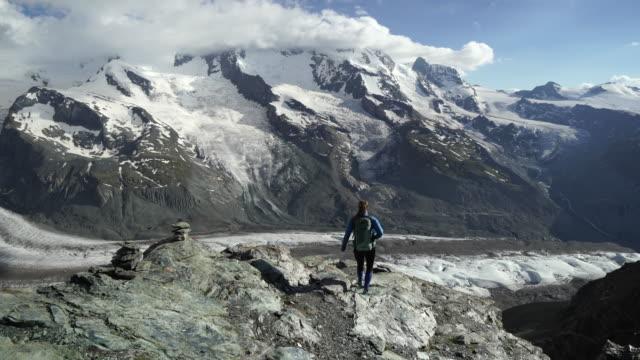 stockvideo's en b-roll-footage met vrouw wandelingen berg boven de gletsjer - zermatt