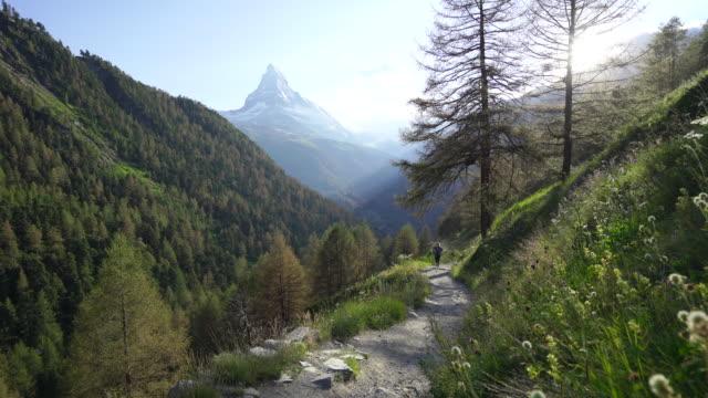 stockvideo's en b-roll-footage met vrouw wandelingen trail met zonnige uitzicht op de zwitserse matterhorn - matterhorn